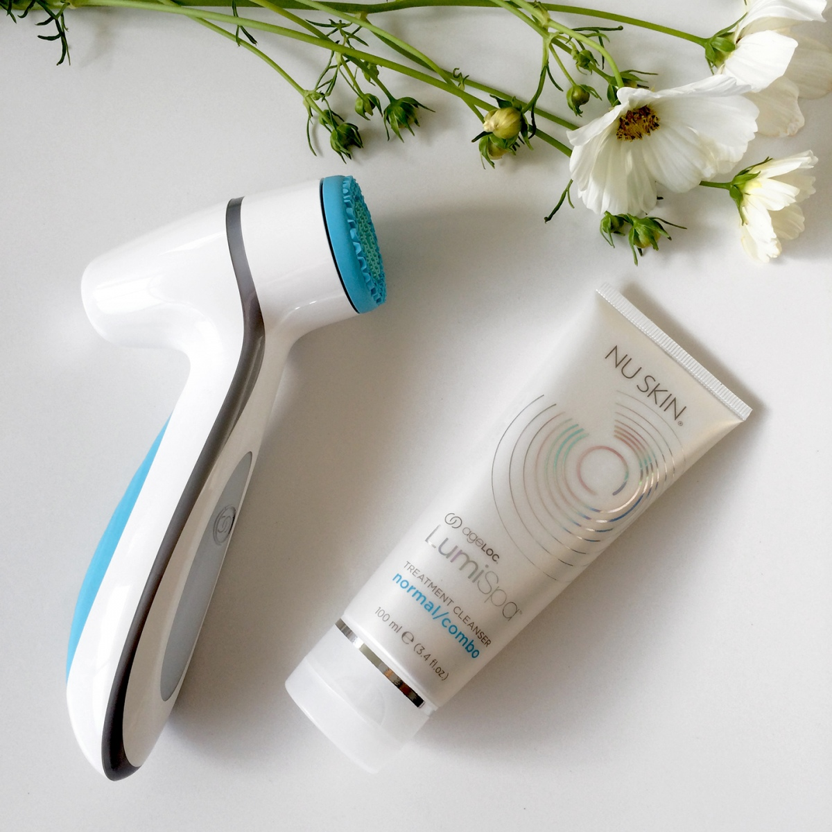 LumiSpa device and cleanser on a white surface with white wild flowers.